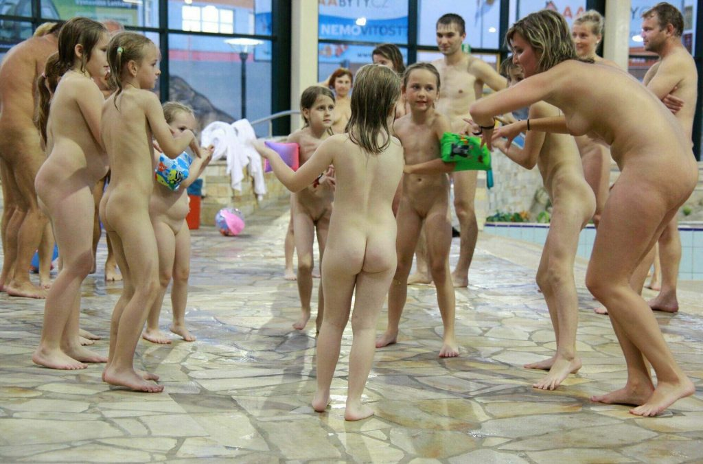 Naturist party - adults and young nudists photo